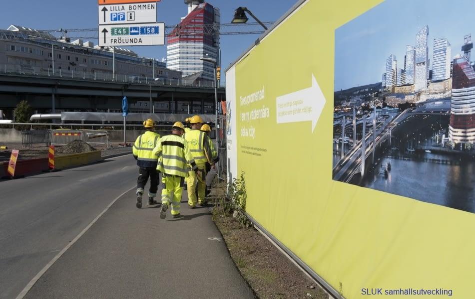 Byggarbetare är på väg till rast. Bakom dem finns en plansch hur det kommer att se ut när Hisingbron är klar.